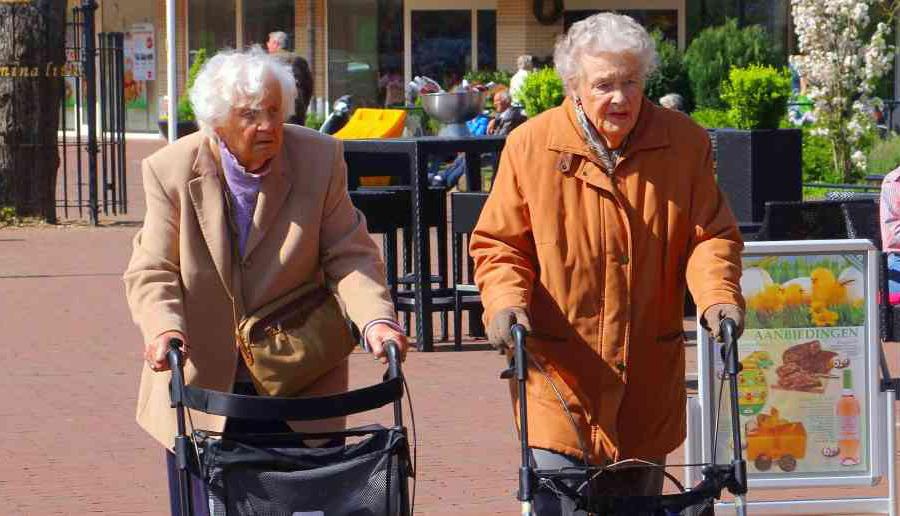 Afbeelding twee oudere vouwen op straat achter een rollator