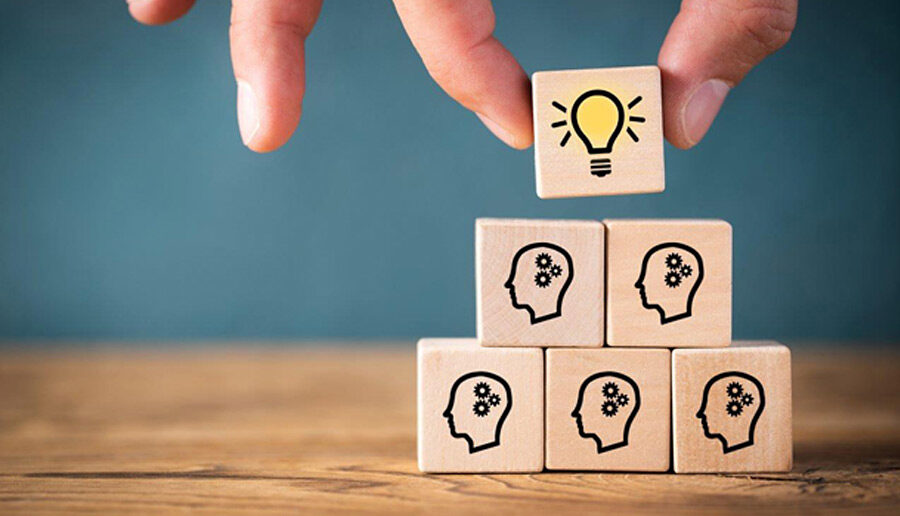 Oplossingen aandragen gesymboliseerd door gestapelde iconen van mensen met bovenaan een lamp icoon, houten blokjes