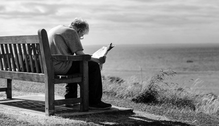 Een oudere man lezend op een bankje